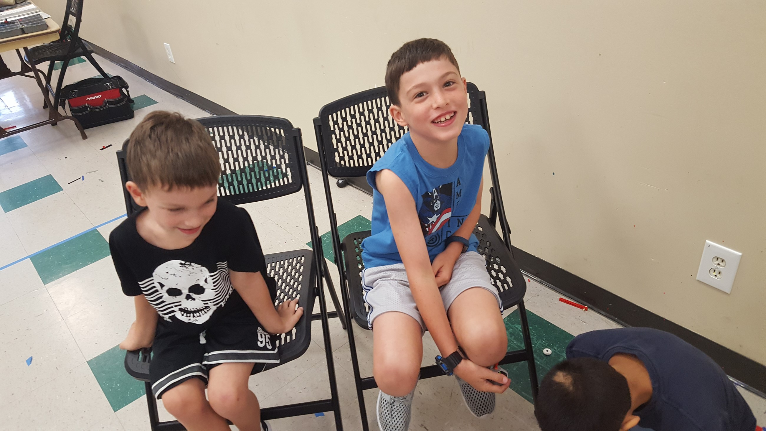 Two children sitting in chairs at camp