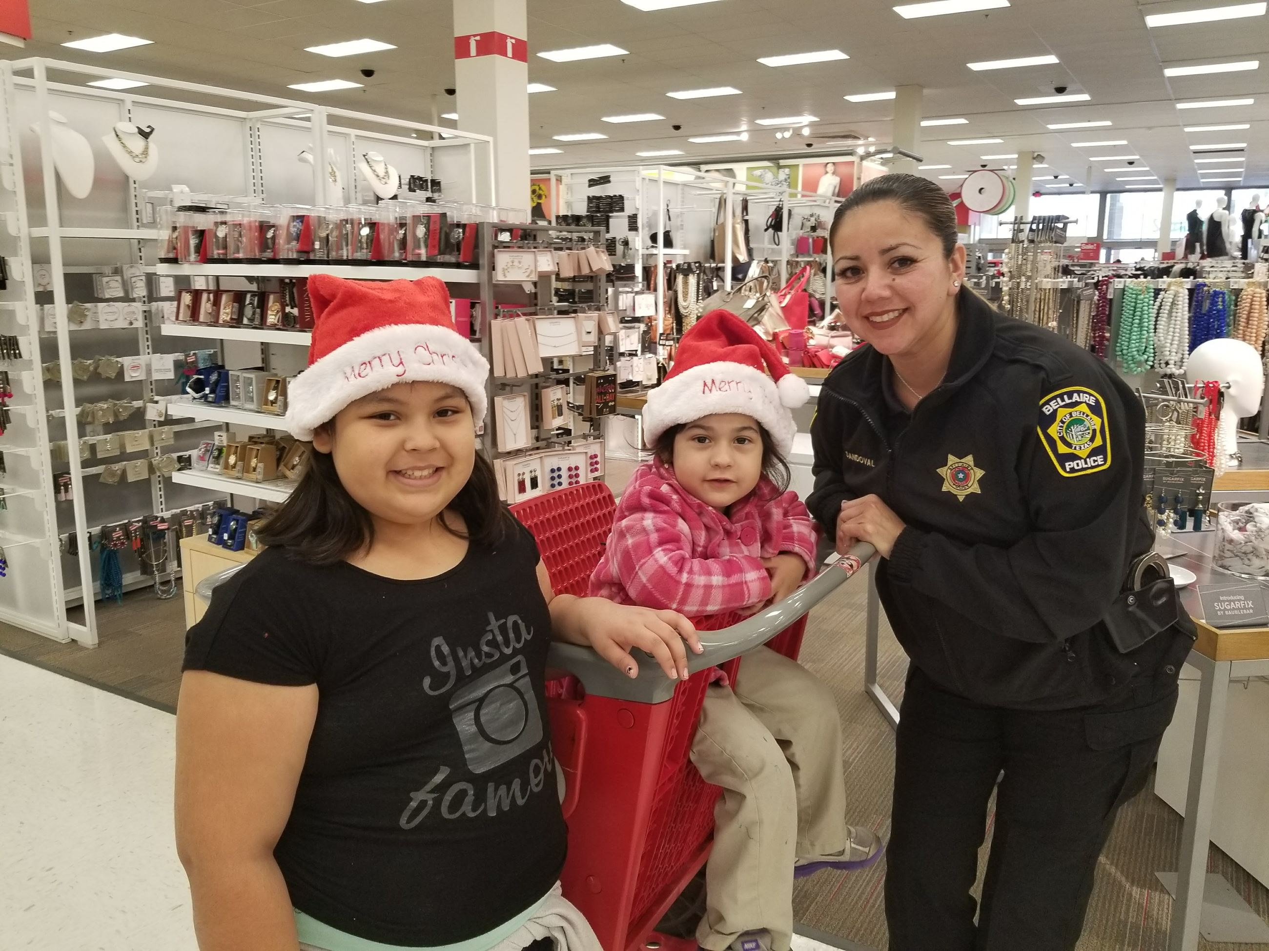 Officer with two little girls at Shop with a Cop event