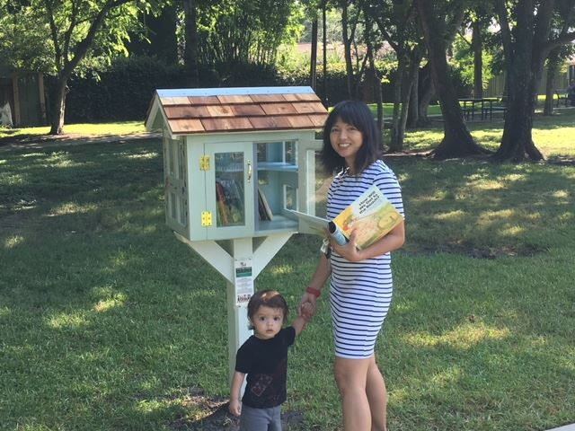 Mother and son picking books from the little free library