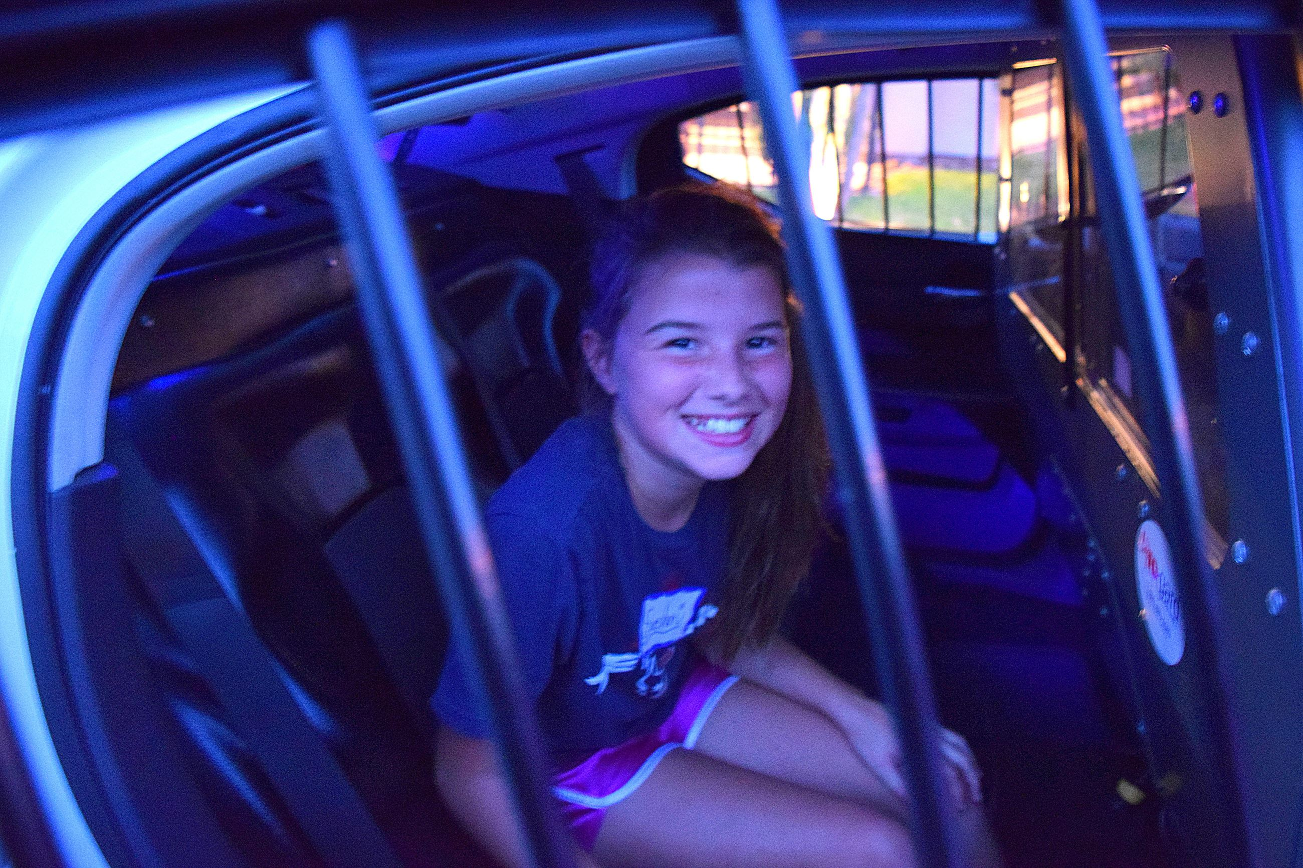 Little girl sits in the back of a squad car