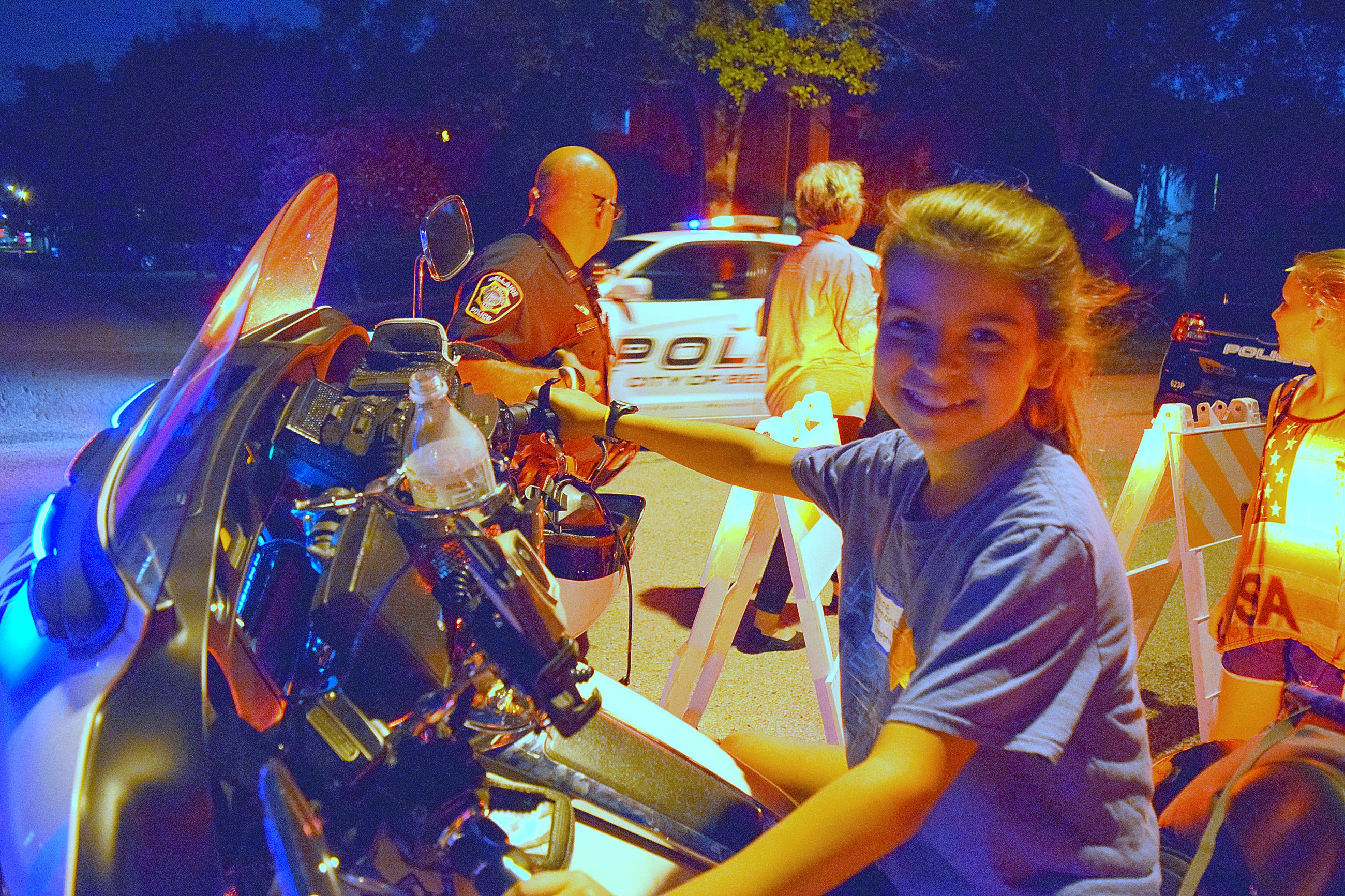Little girl poses on Police motorcycle